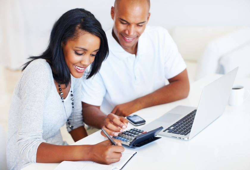 Portrait of young couple calculating their monthly expenses at home